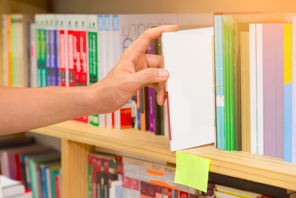 本棚から本を取り出している