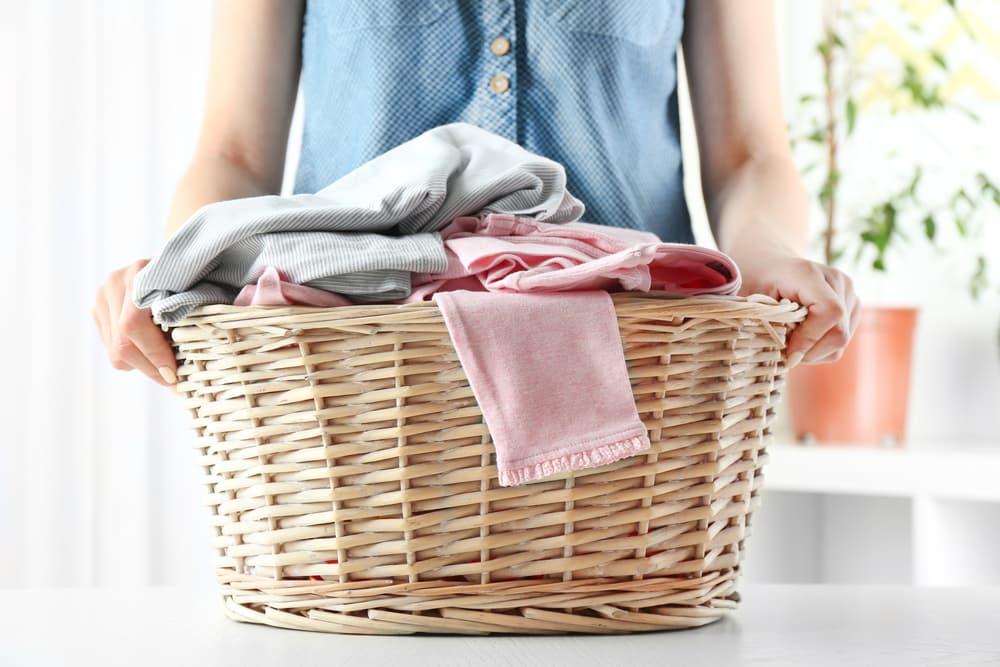 衣類の入った洗濯かごを持っている