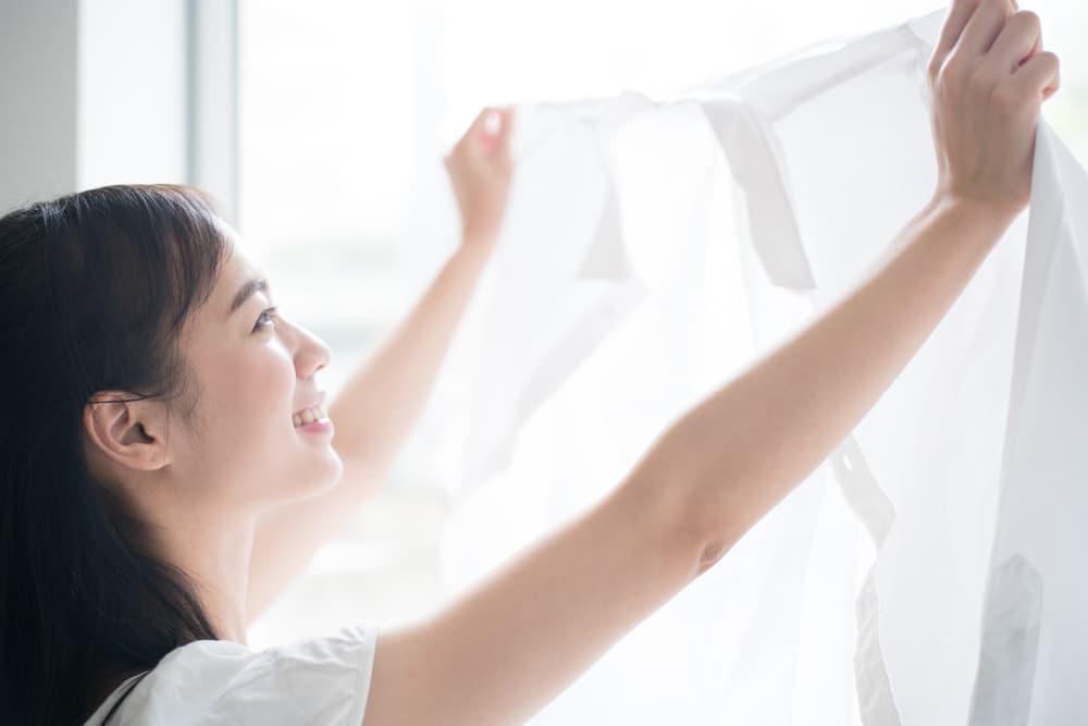 真っ白な洗濯物を干している女性