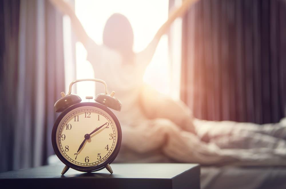 朝日が差し込む部屋と目覚まし時計