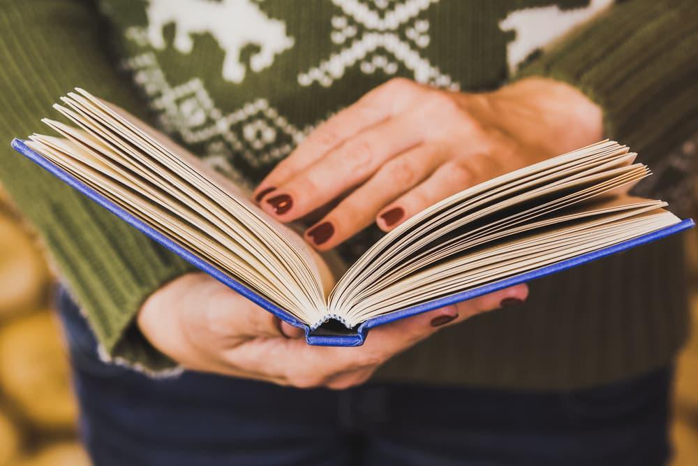 本を読んでいる女性の手のアップ
