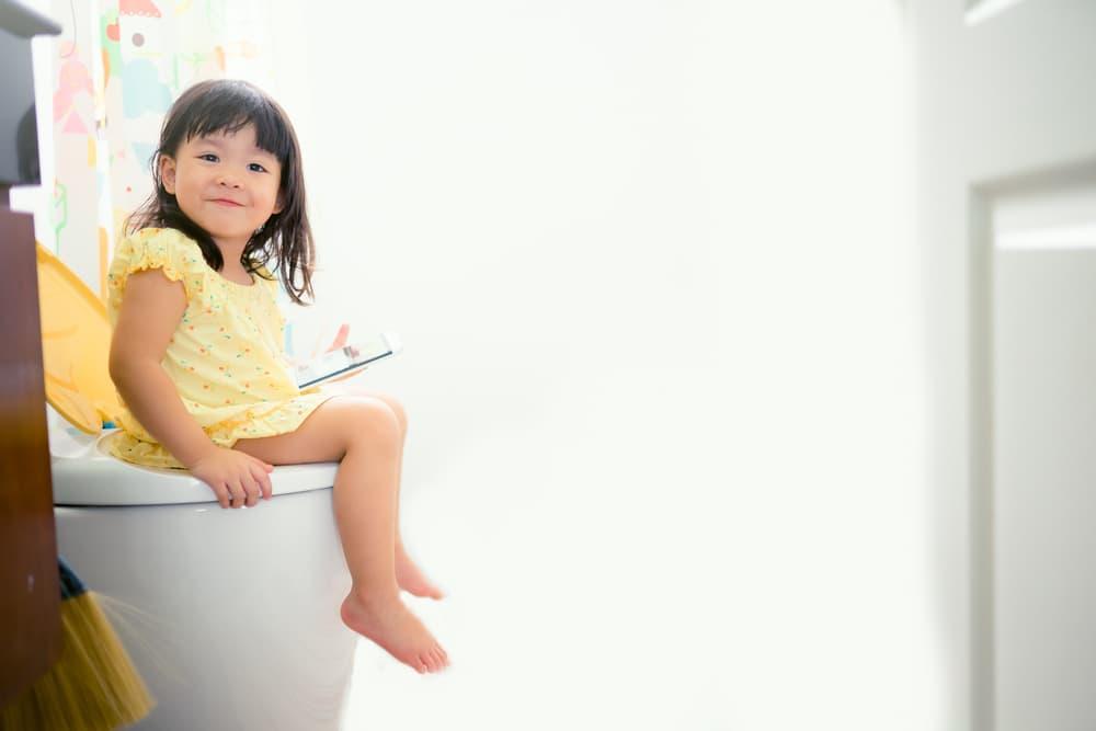 子供がトイレに座っている