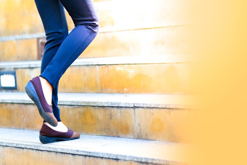 駆け足で階段をあがる女性