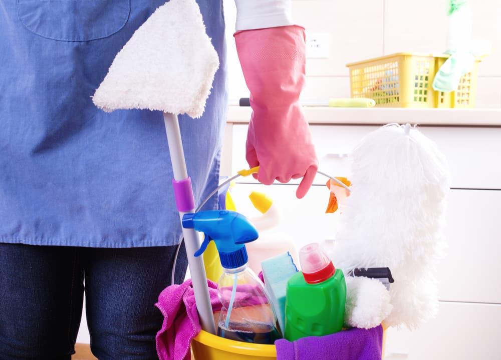 エプロンとゴム手袋をして掃除道具を持つ人