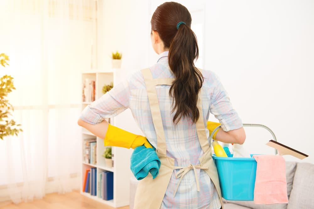 掃除道具を手にした女性の後ろ姿