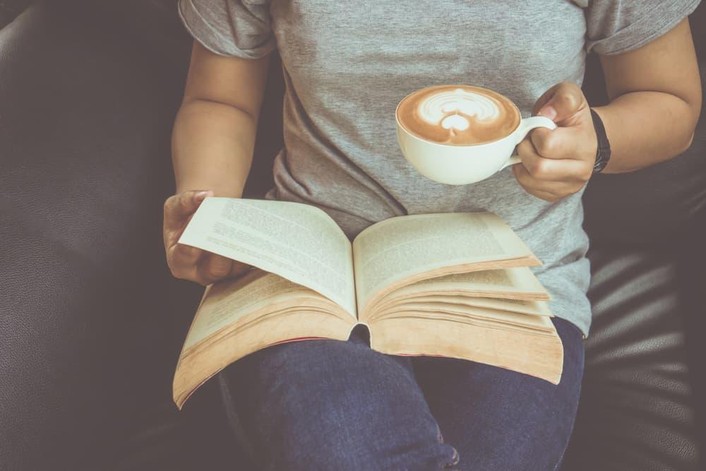 コーヒーを飲みながら、読書をしている女性