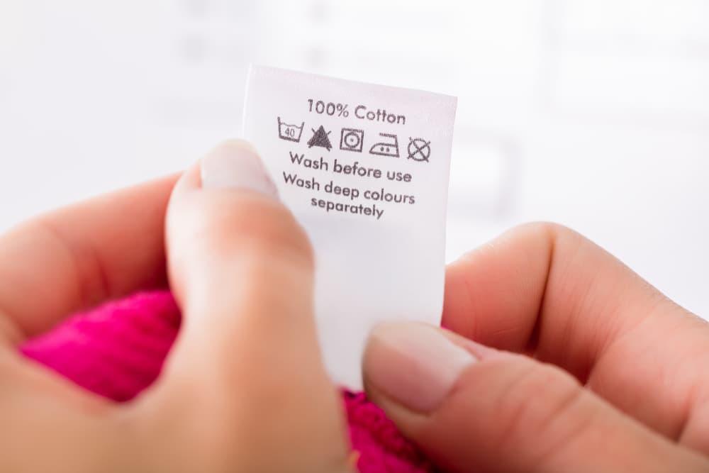 衣類の表示タグを持つ女性の手元