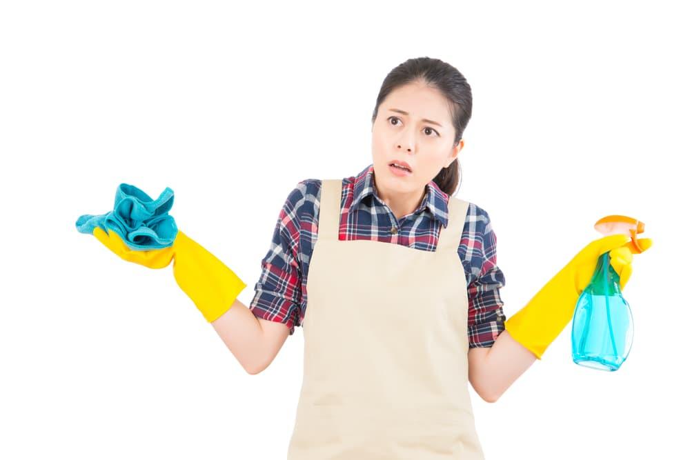 掃除用具を手に困った女性