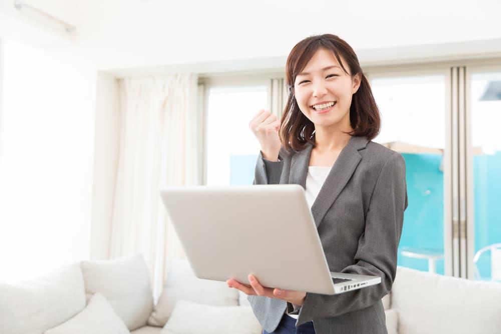 パソコンを手にしたスーツ姿の女性