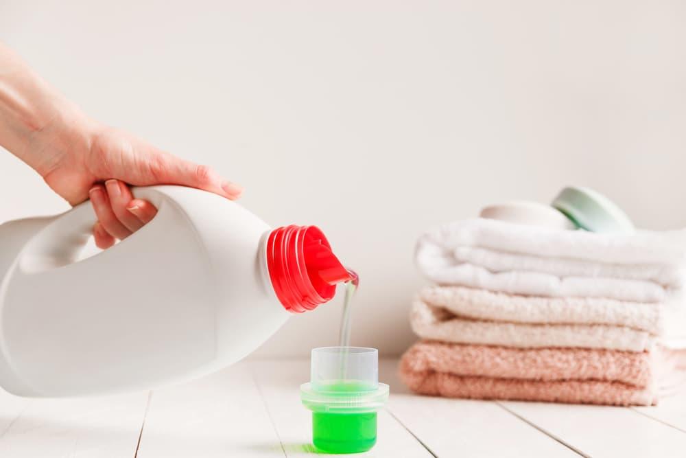容器から計量カップに液体洗剤を入れている