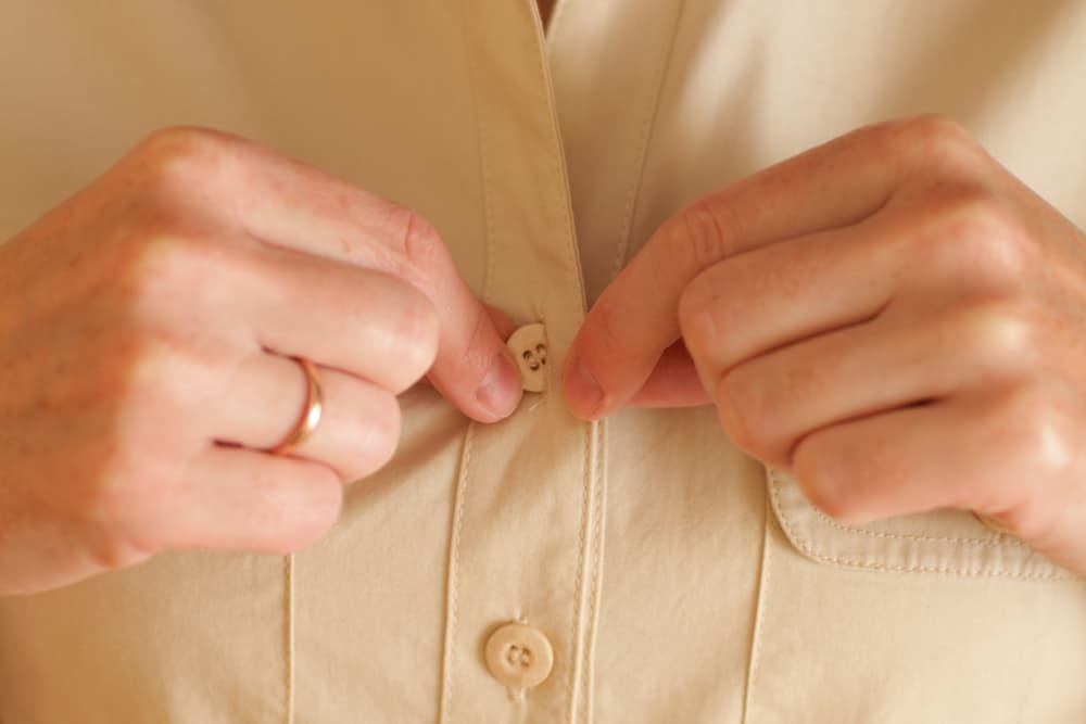 ワイシャツのボタンを閉めている手元