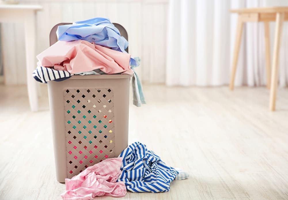 洗濯カゴいっぱいに衣類が詰め込んである