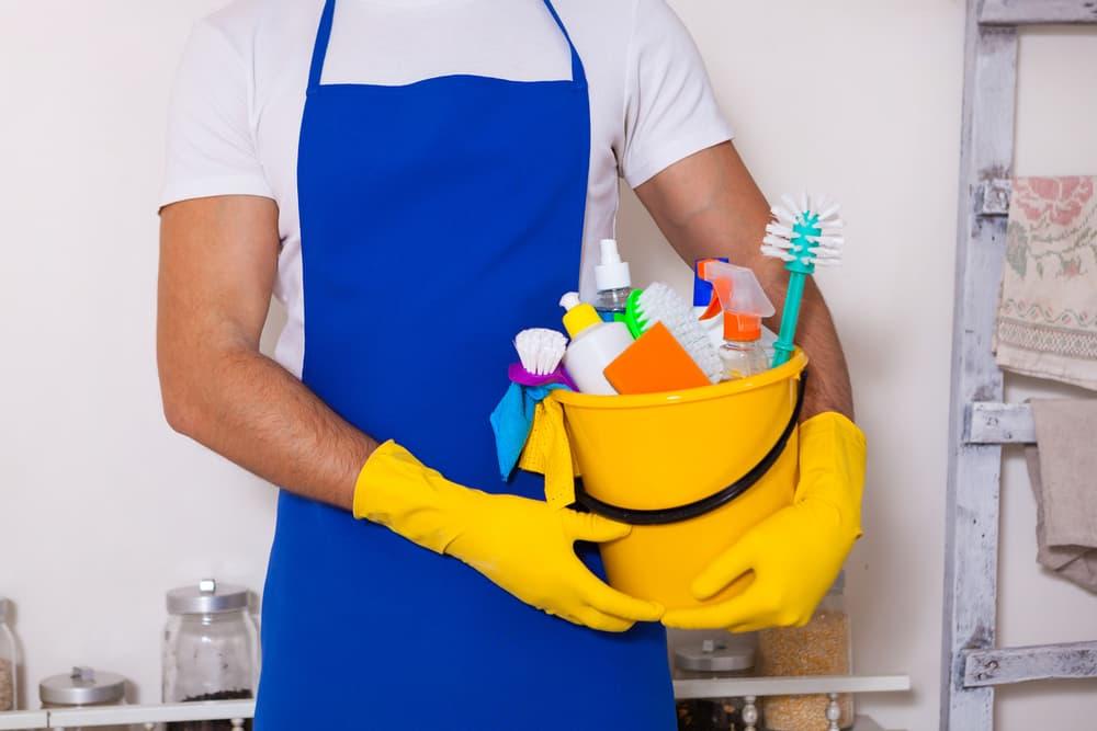 エプロン姿の男性が掃除道具を抱えている