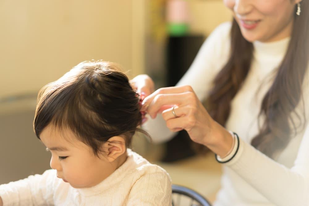 子どもの髪の毛を結んでいる女性
