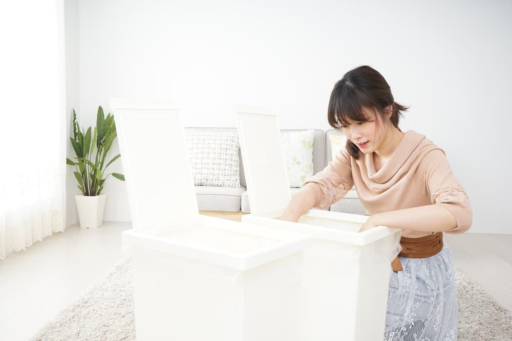 女性が白いごみ箱を開いている