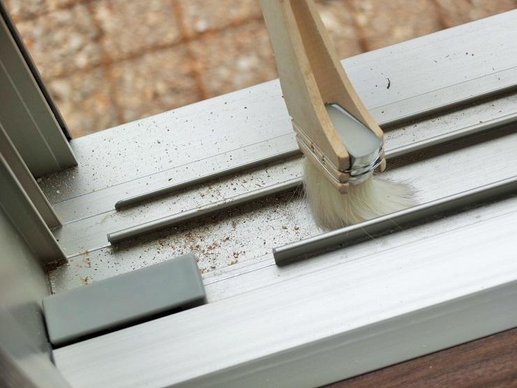 窓サッシのホコリをブラシでかき出す
